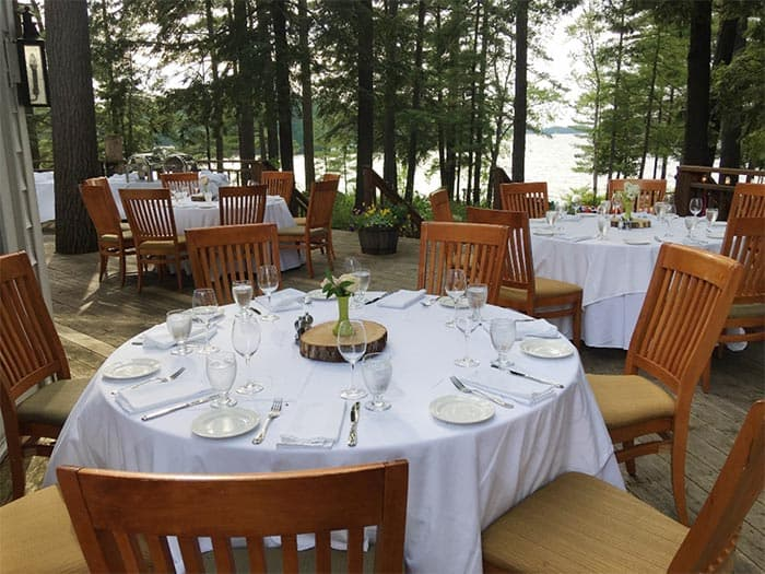 Some nice fancy dining tables set up under the trees, next to a lake