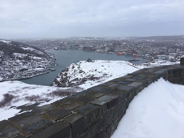 A wintery view of a city from the top of a nearby hill